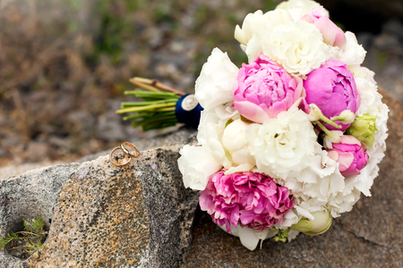wedding rings lie on a stone in front of a bouquet of flowers Stock Photo