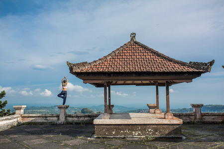 woman practicing yoga in the traditional balinesse gazebo Stock Photo