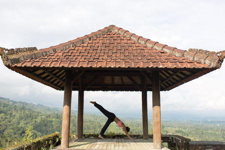woman practicing yoga in the traditional balinesse gazebo 스톡 콘텐츠