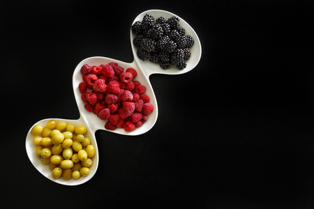 juicy raspberry, blackberries and dogeberry in white plate on black background