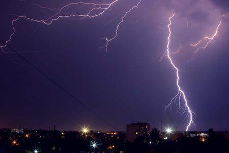 Lightning storm over the city in purple light