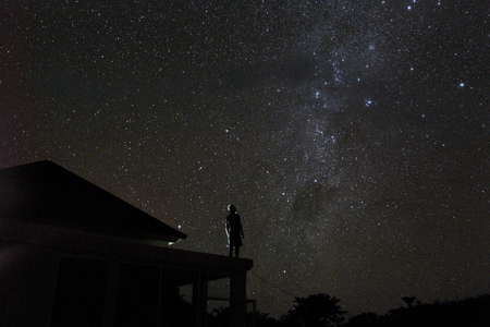 alone woman on rooftop watching mliky way and stars in the night sky on Bali island.