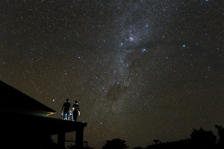 Couple on rooftop watching mliky way and stars in the night sky on Bali island. Stock Photo