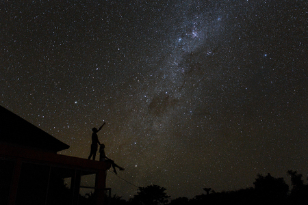 Couple on rooftop watching mliky way and catching stars in the night sky on Bali island. Standard-Bild