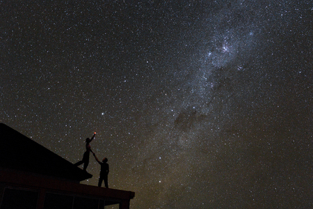 Couple on rooftop watching mliky way and catching stars in the night sky on Bali island. 写真素材