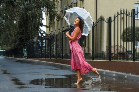 Young girl in a red dress with a transparent umbrella dancing in the rain standing in a puddle. Stok Fotoğraf