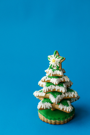 Blue chirstmas tree gingerbread cookie on blue background. Holidays food and decoration concept.