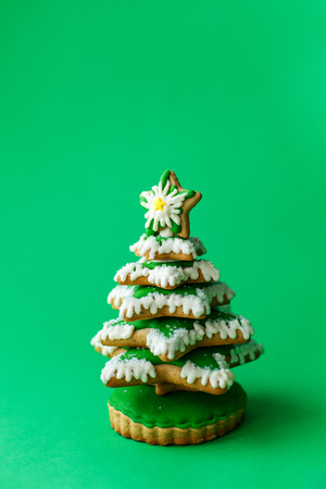 Greenchirstmas tree gingerbread cookie on green background. Holidays food and decoration concept. Stock Photo
