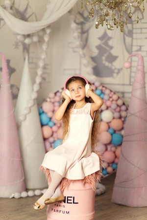 Portrait of cute little princess in headphones. Studio background with balls and cones.