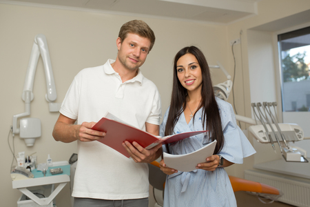 doctor and his assistant looking in folder with paper. Dental office background Stock Photo