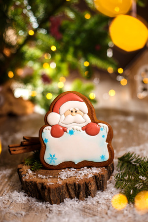 Holiday traditional food bakery. Gingerbread santa claus with copy space in cozy warm decoration with garland lights. 스톡 콘텐츠