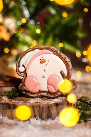 Holiday traditional food bakery. Gingerbread happy sitting Snowman or snowball in cozy warm decoration with garland lights.