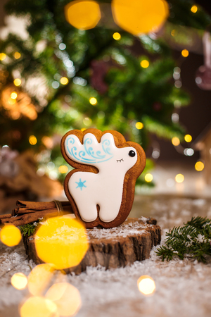 Holiday traditional food bakery. Gingerbread white christmas deer in cozy warm decoration with garland lights.