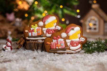Holiday traditional food bakery. Gingerbread two chirstmas postman and sleigh with gifts in cozy warm decoration with garland lights.