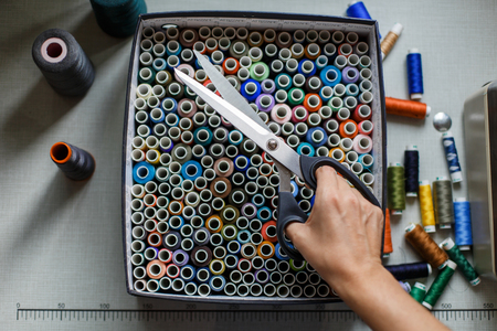 A seamstress pulls a pair of scissors out of a box with skeins of colored threads.Sewing industry.