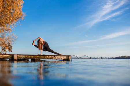 Young woman practicing yoga exercise at quiet wooden pier with city background. Sport and recreation in city rush.