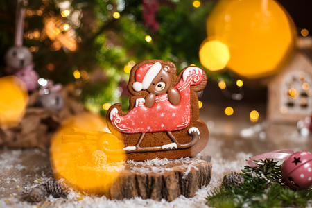 Holiday traditional food bakery. Gingerbread christmas bear in sleigh in cozy decoration with garland lights.