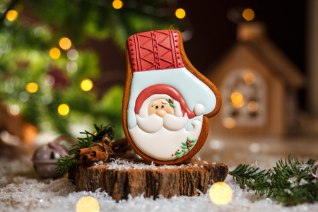 Holiday traditional food bakery. Gingerbread Santa glove in cozy warm decoration with garland lights. Stock Photo