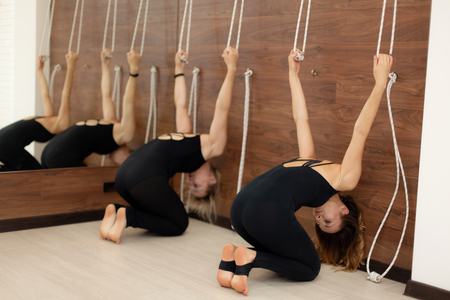 woman practicing yoga on ropes stretching in gym. Fit and wellness lifestyle.