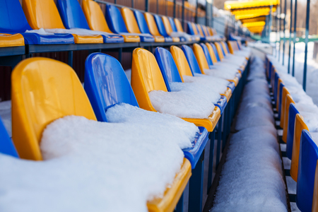 colored seats snow covered in winter snowy stadium. Snow covered tribune. 免版税图像