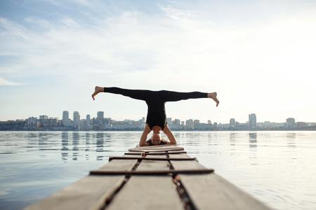 Young woman practicing yoga exercise at quiet wooden pier with city background. Sport and recreation in city rush. Reklamní fotografie - 116220671