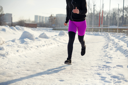 girl in sportswear run on a snow-covered stadium Fit and sport lifestyle. Run and listening music. Sport lifestyle.