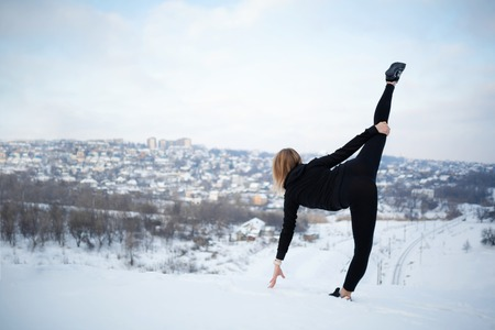 Young caucasian female blonde in leggings stretching exercise on open air in snowy forest. fit and sports lifestyle.