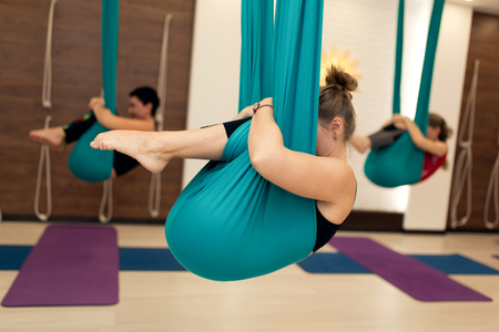 a group of women are hanging in a fetal position in a hammock. fly yoga class in the gym. Fit and wellness lifestyle. Stock Photo