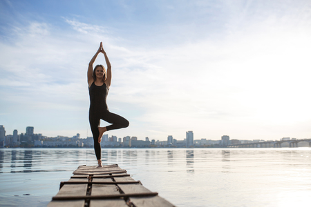 Young woman practicing yoga exercise at quiet wooden pier with city background. Sport and recreation in city rush. Reklamní fotografie - 118131383