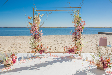 Event decoration. Wedding chuppa at riverside decorated with fresh flowers. Florist workflow.
