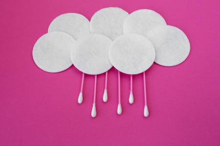 top view on pink cotton buds with white heads and white round cotton disks laid out in clouds with rain drops on a pink background. Stok Fotoğraf