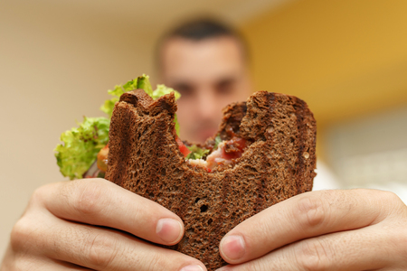 Closeup funny blurred protrait of young man hold bitten sandwich by his two hands. Sandwich in focus. light background Standard-Bild