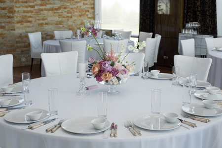 Event white restaurant table served and decorated with delicate fresh flowers. Stock fotó