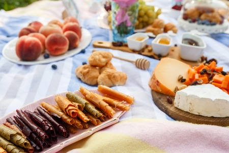 Summer picnic blanket with tasty food and snacks on it. Summer weekends.