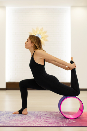 young woman in a sportswear yoga exercises with a yoga wheel in the gym. Stretching and wellness lifestyle.