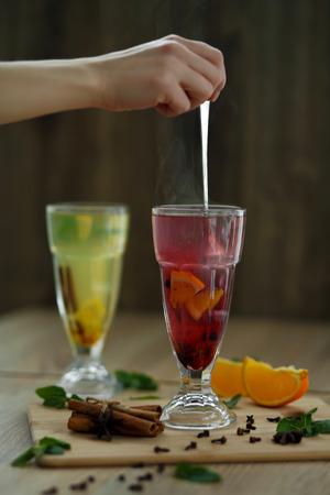 hand stirs hot steaming tea in glass. winter hot seasonal drinks.