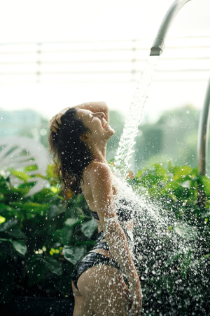 Sexy slim female in swimsuit takes shower in swimming pool between green bushes on rooftop with city scape background.