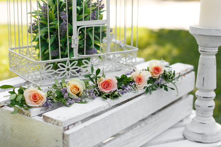 Festive rustic style decorations fresh flowers and white birdcage on a wooden box. Sunny summer day.
