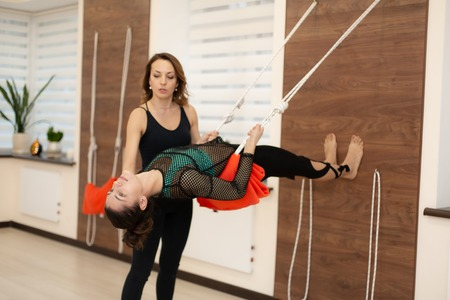 coach helps woman practicing yoga on ropes stretching in gym. Fit and wellness lifestyle. Reklamní fotografie