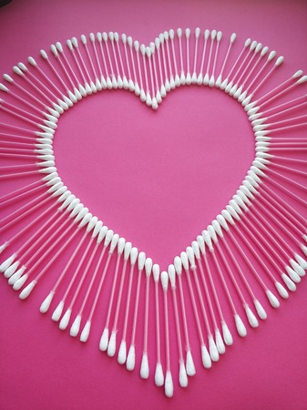 cotton buds laid out in the shape of a heart on a pink background.
