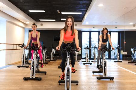 Un gruppo di giovani donne magre si allenano sulla cyclette in palestra. Concetto di stile di vita sportivo e benessere.