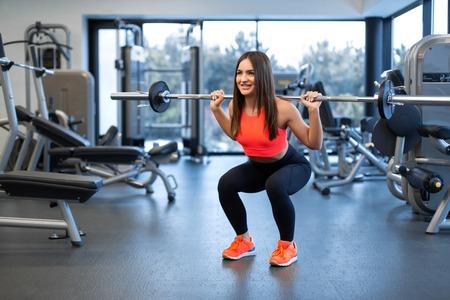 mujer joven hermosa delgada en ropa deportiva se pone en cuclillas con una barra en el hombro en el gimnasio. Foto de archivo