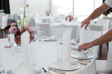 The waiter in the restaurant set up a table for guests. Waiters hands are a white tablecloth, napkins, white dishes and a bouquet of flowers on the table in the frame.