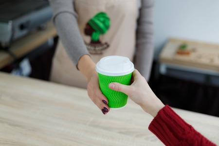 Barista in apron is giving hot coffee in green takeaway paper cup to customer. Coffee take away at cafe shop.
