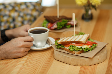 man takes a cup of coffee from a wooden table, on which lies a sandwich.