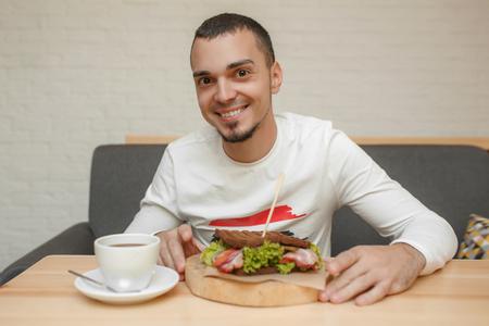 Happy man in cafe will eat sandwich.