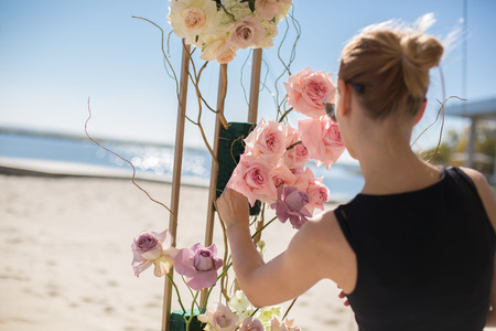 Florist girl decorates wedding arch with fresh flowers on the sandy shore of the lake. Wedding florist decorators workflow. Banco de Imagens - 120694912