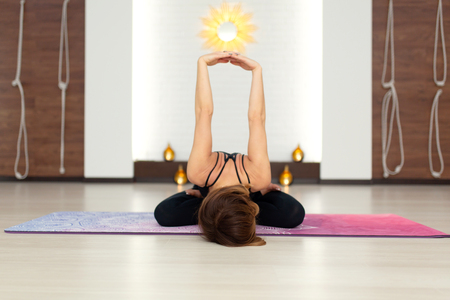 Young woman practicing yoga stretching in gym. Fit and wellness lifestyle.