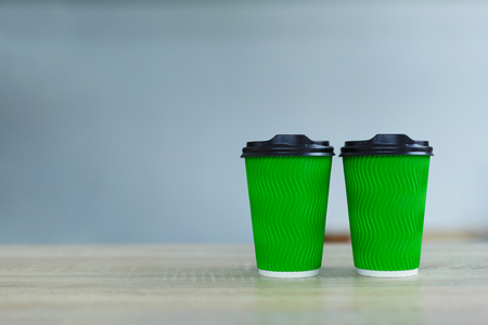hot coffee in green takeaway paper cup. Coffee take away at cafe shop.