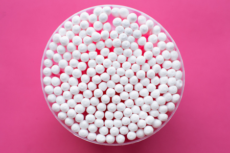 Primo piano dall'alto sulla confezione rotonda di cotton fioc su sfondo rosa.
